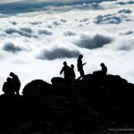 Tourists enjoy being above the clouds during an undercast